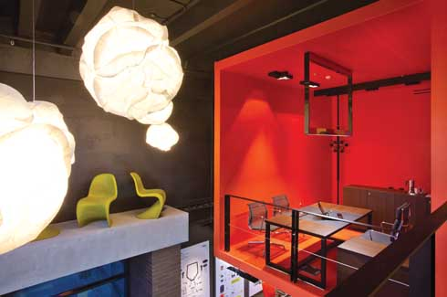 The bright red cube contrasts the furniture display and light fixtures, adding to the colourful drama.