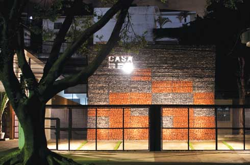 The Casa Rex logo stands out of the façade designed from gabions made of red sandstone and grey gravel.