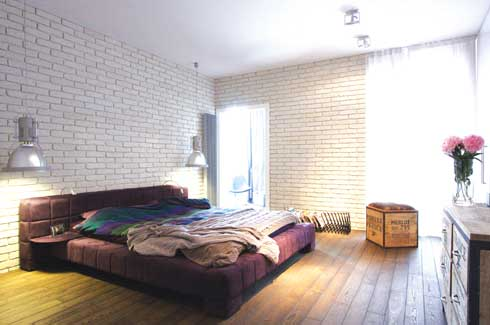 A purple bed finds a spot in the bare loft look of the room. Textures, like that of the brick wall and the plain cupboard both in pristine white, create a dynamic dialogue which is really the essence of the decor.
