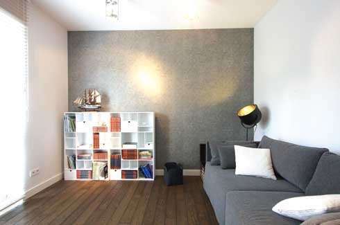A grey focus wall creates depth in the room. The furniture comprising of steel shelves and a comfortable grey sofa gives a chic appeal to the room.