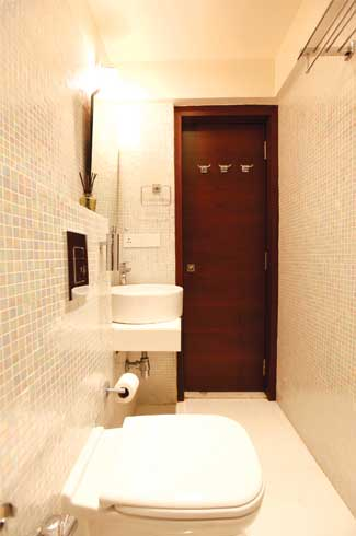 You can always bargain for extra space in small ways like concealing the flush tank in the bund wall, as in this bathroom.