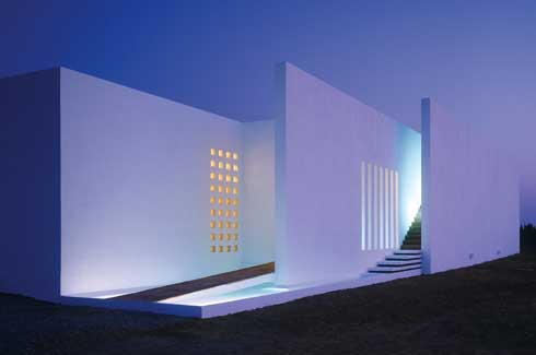 A night view of the three parallel surfaces that make up the Fobe House façade.