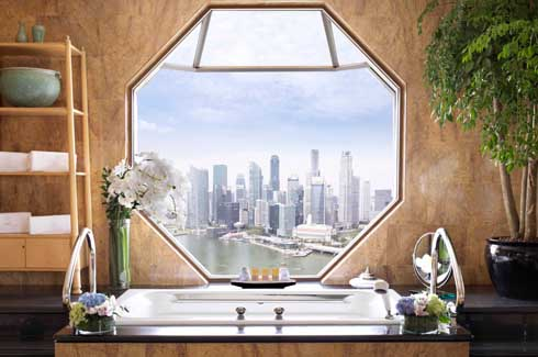 The bathrooms of all 608 rooms and suites are characterised by octagonal windows that breathlessly overhang Marina Bay.