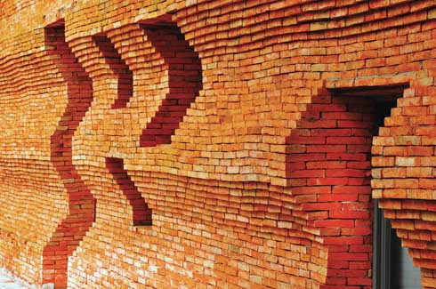 The eight metre high, hand-made brick walls have several eometrically shaped negative spaces to mitigate heat and provide casual spaces for the students to sit in.