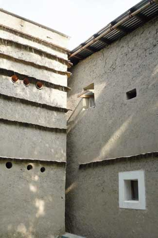 The cob walls have windows and small openings for natural light and ventilation.