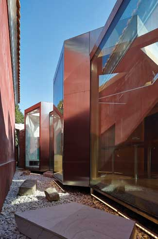 Glass panels placed at varied angles reflect the historic red wall that make up the backdrop of the teahouse.