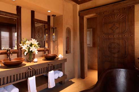 Dark wood and subtle colours bring charm to this luxurious and spacious, double sink equipped bathroom of a villa.
