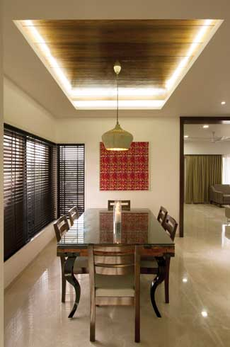 Common areas like the dining and living room maintain a formal air and are marked by beautiful marble and diffused lighting. The eye-catching pendant light over this dining table was sourced from Mumbai.