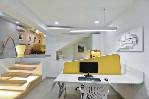 The workstations find a cosy niche in their split-level space, where yellow shades of walls and partitions warm up the white decor.